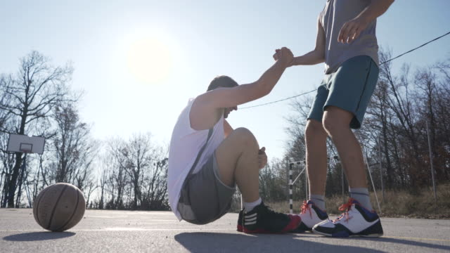 Man helps his friend to stand up Two men playing basketball on a beautiful sunny day. physical injury stock videos & royalty-free footage