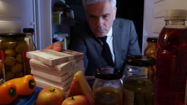 POV Man hiding stacks of UK pounds in a fridge video