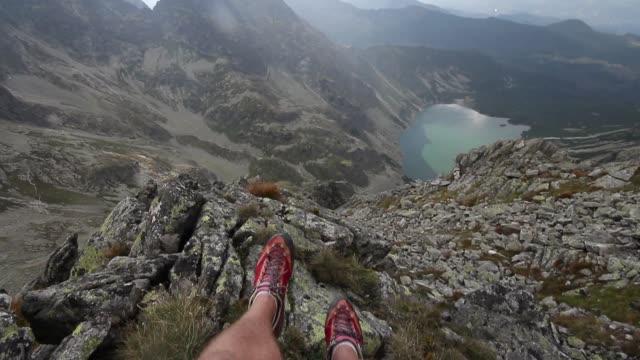 tatra dağları milli parkı polonya seyahat yolculuk tutkusu vadide bir manzaralı bir uçurumun kenarında oturan adam uzun yürüyüşe çıkan kimse - zakopane stok videoları ve detay görüntü çekimi