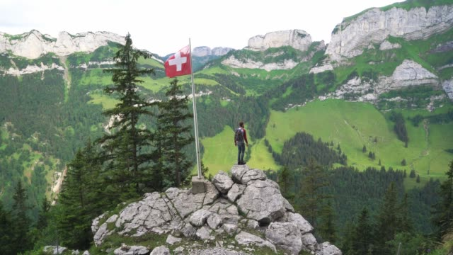 man hiking in swiss alps in appenzell - bandiera nazionale video stock e b–roll