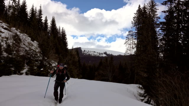man hiking in the winter mountains video