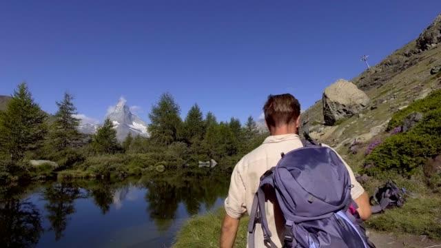 stockvideo's en b-roll-footage met man wandelen in zermatt zwitserland loopt pas prachtig bergmeer - zermatt