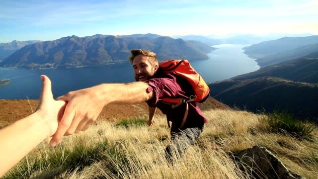 uomo escursioni su terreni difficoltosi, per ricevere assistenza scrivete a mano - fiducia video stock e b–roll