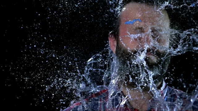 slo mo uomo di colpire in viso con acqua palloncino - ritemprarsi video stock e b–roll