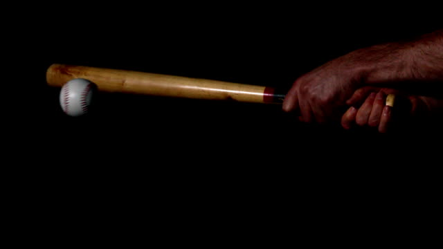 Man hitting baseball with bat on black background video