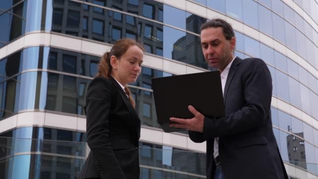 vidéos et rushes de homme tenir l'ordinateur portatif dans les mains, expliquer à la femme, deux personnes regardant sur l'écran - enseignant(e)