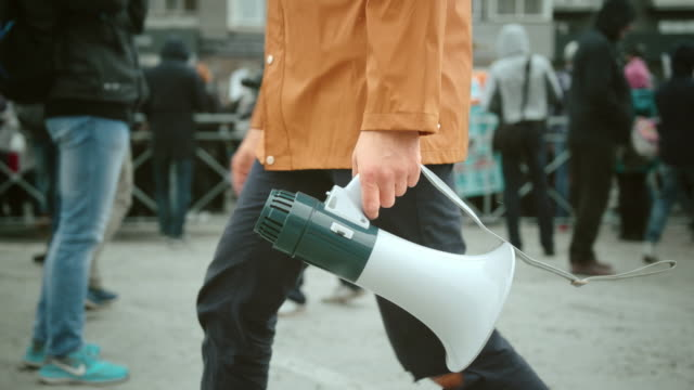 Man hold megaphone and shouting close up. Rebel loudspeaker on political strike. Man walk and hold megaphone in hand and shouting closeup. Screaming man. Crowd people day demonstration. Rebel go shout loudspeaker strike protest close up. Revolution in city street. Political rally. megaphone stock videos & royalty-free footage