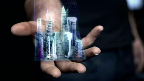 vídeos de stock e filmes b-roll de man holding 3d city hologram in his hand - futurista