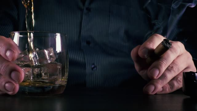 a man holding a glass and a cigar slow motion - scotch whisky video stock e b–roll