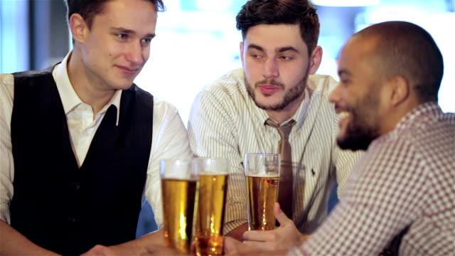 Man holding a glass of beer in hand while sitting at the bar video