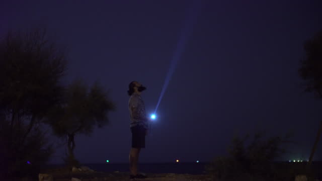 A man holding a torch to the dark sky A man holding a torch to the dark sky flashlight stock videos & royalty-free footage
