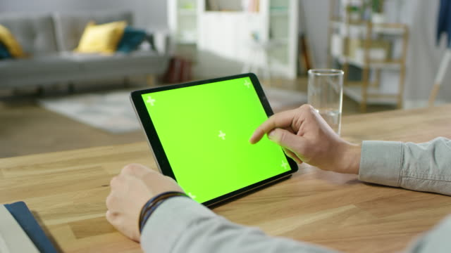Man Holding and Using Hand Gestures on Green Mock-up Screen Digital Tablet Computer While Sitting at the Desk. Man Buying stuff or Browsing Through the Internet. In the Background Cozy Living Room.