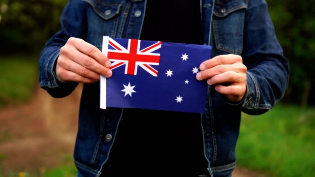 Man holding Australian flag outdoors. Independence Day, or national holidays concepts