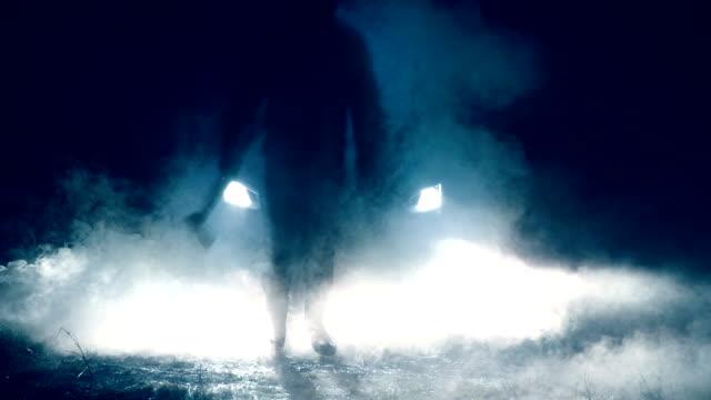 stockvideo's en b-roll-footage met man met bijl staan voor auto - mist donker auto
