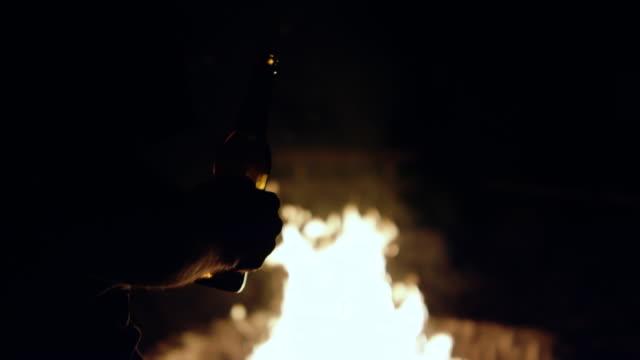Mann mit Bier vor einem Lagerfeuer – Video