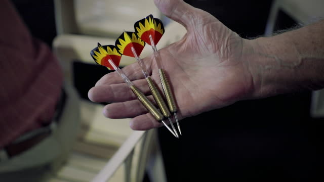 A man holding darts