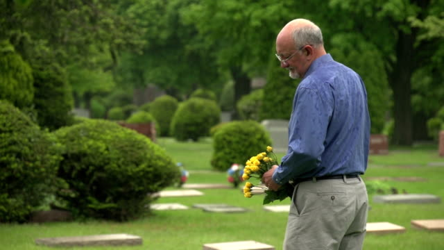 Man holding flowers at cemetery in the rain video