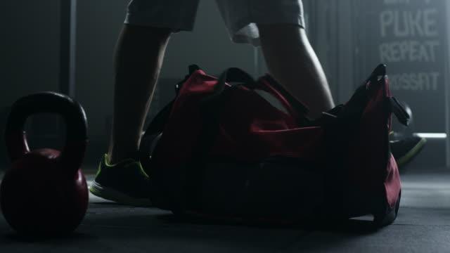 Man holding gym bag coming to treining video