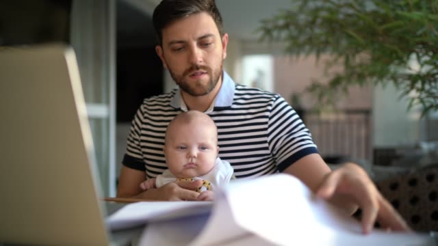 Man holding his newborn son and working with laptop at home