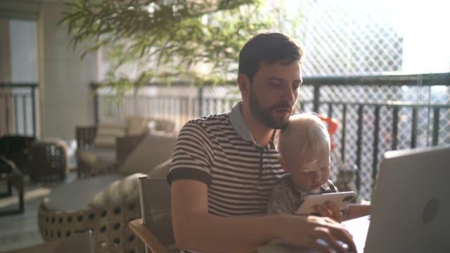 vídeos y material grabado en eventos de stock de hombre sosteniendo a su hijo y trabajando con la computadora portátil en casa - foto natural