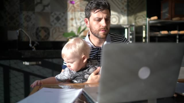Man holding his son and working with laptop at home