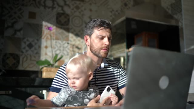 Man holding his son and working with laptop at home Man holding his son and working with laptop at home real life stock videos & royalty-free footage