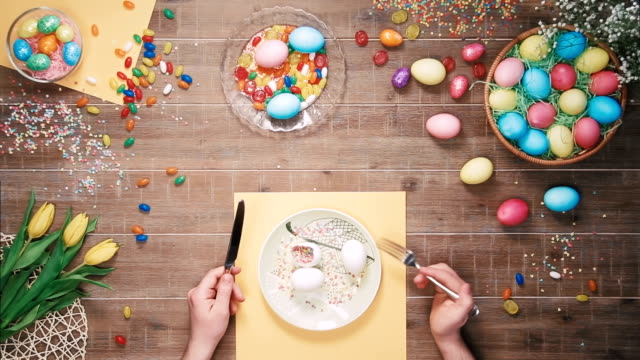 Man holding knife and fork before plate with easter eggs on table decorated with easter eggs. Top view video