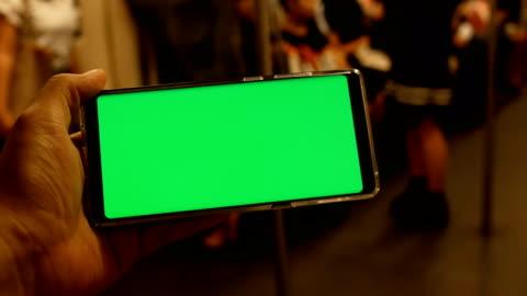 uomo in possesso di cellulare con schermo verde sul treno - composizione orizzontale video stock e b–roll