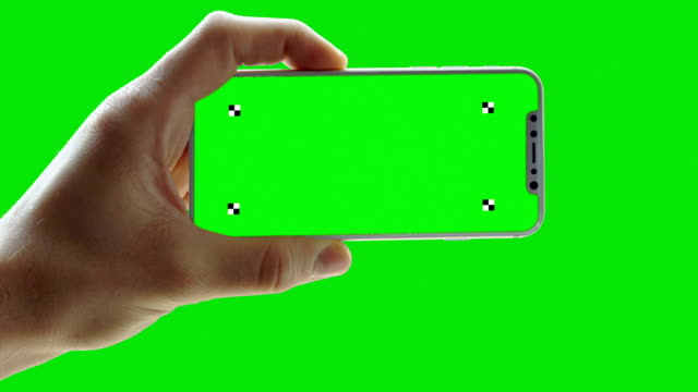 Man holding phone on green screen. Trackers Close up on phone with green screen and trackers iphone stock videos & royalty-free footage