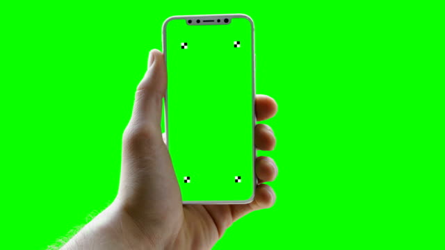 vídeos de stock e filmes b-roll de man holding phone on green screen. trackers - hand