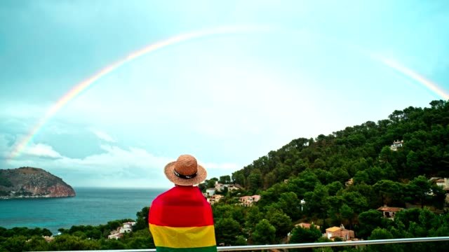 Man holding Rainbow flag over real Rainbow Man is looking at the view, holding a rainbow flag bisexuality stock videos & royalty-free footage
