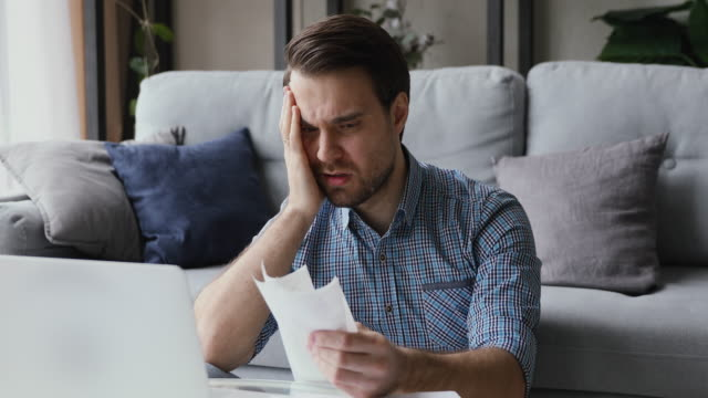Man holding receipts feel frustrated due money overspend Man sitting in living room do finance analysis holds sales slip heap of receipt feels frustrated worried due lack of money, small business entrepreneur bankruptcy financial problems, overspend concept bills and taxes stock videos & royalty-free footage