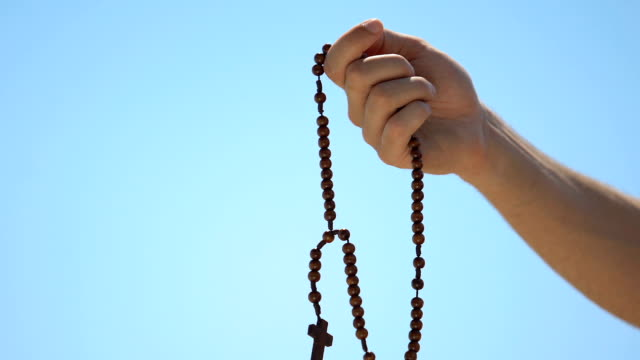Man holding rosary praying to god on sky background, atonement for sin, closeup