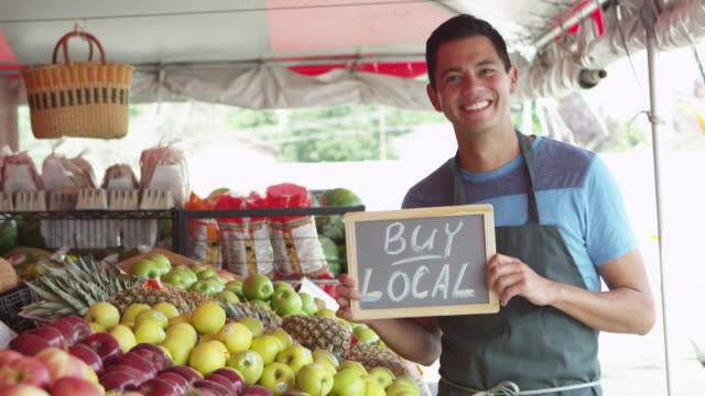 Man holding sign saying buy local from fruits market video