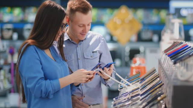 mężczyzna trzyma inteligentny telefon i wskazuje na inny telefon, który jest w rękach kobiety. wnętrze sklepu technologicznego - evaluation filmów i materiałów b-roll