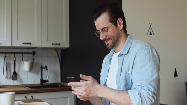 mann halten smartphone genießen entfernte informelle angenehme chat mit freund - bucht stock-videos und b-roll-filmmaterial