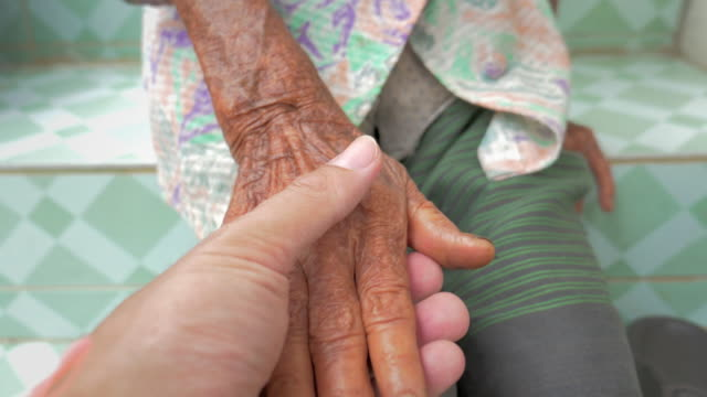 Man holding the hand of the senior woman in his hand video