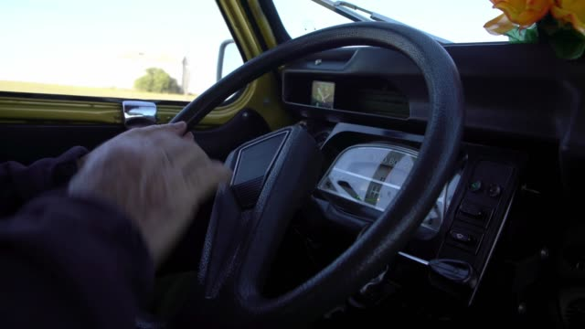 4K, Man holding the steering wheel of an old car with the dashboard in view.