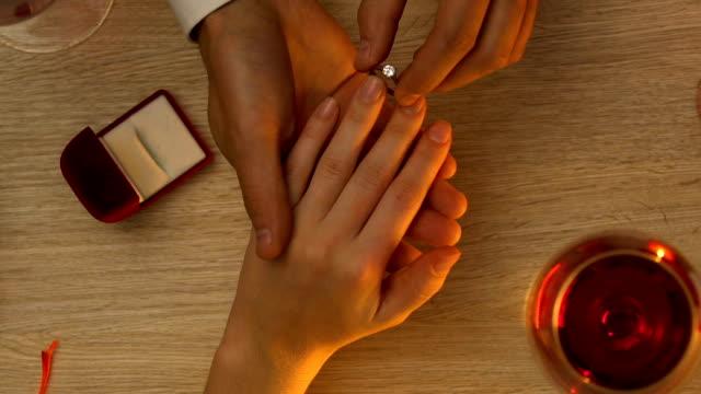 梨花の手を握って、ロマンチックな夕食時に婚約指輪を着用の男 - 指輪点の映像素材/bロール