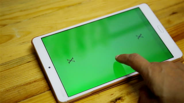 man holds a blank tablet PC with a green screen video