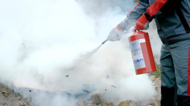 a man holds a fire extinguisher in his hands and extinguishes the fire box with a foam, the fire is stopped with a safety device - gommapiuma video stock e b–roll