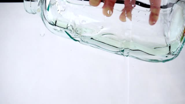 A man holds a jar in his hand and pours water into it, close-up slow motion A man holds a jar in his hand and pours water into it, close-up slow motion on white background, full HD twisted stock videos & royalty-free footage