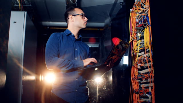 Man holds a laptop, checking wires at a data center, close up. video