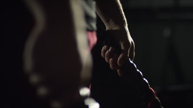 stockvideo's en b-roll-footage met een man houdt battle touwen in zijn handen en zich voorbereidt op werken - touw