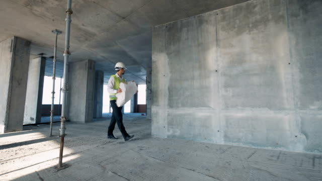 A man holds blueprint while walking in a building, close up.