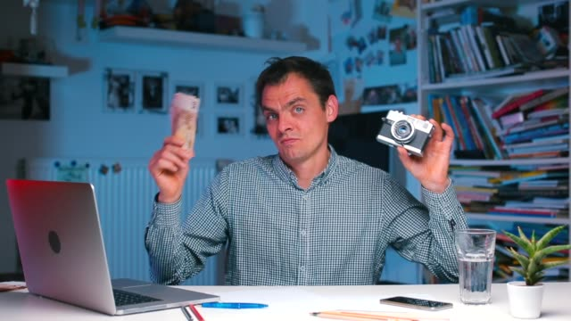 man holds money and a camera in his hands