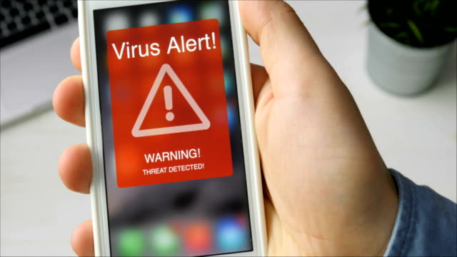 man holds smartphone with virus alert warning sign on the display - настороженность стоковые видео и кадры b-roll