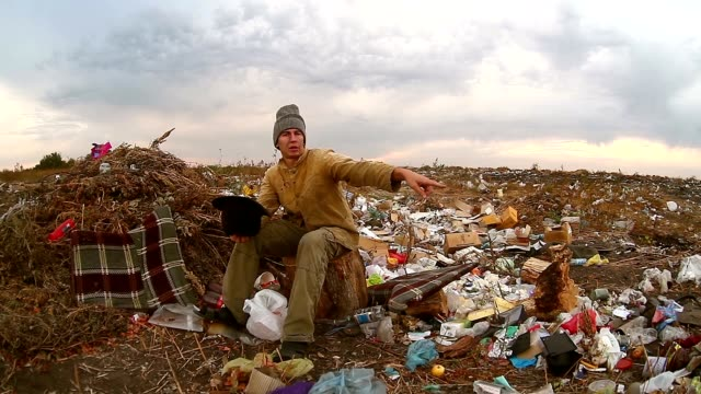 man homeless beggar sitting in a landfill with a hat asks for money food waste video
