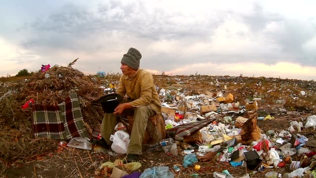 man homeless beggar sitting in a landfill with a hat asks for money food waste truck rides video