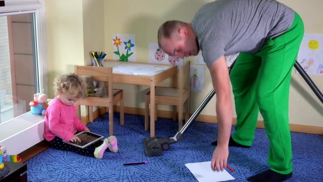 Man hoover child room and little girl play with tablet computer sitting on floor ビデオ